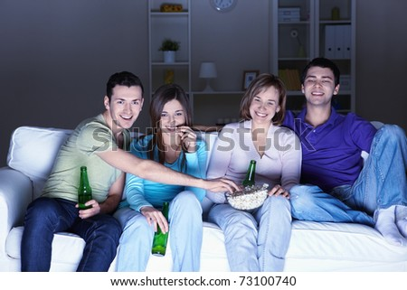 Young people watch TV at home - stock photo