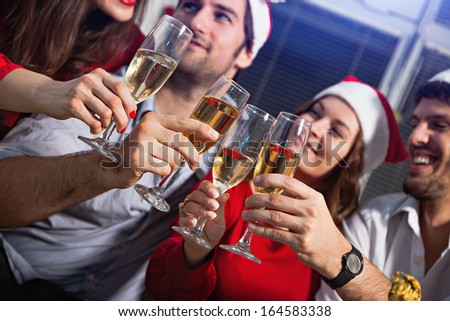 Young people wearing Santa's hats having a toast with champagne on new year's eve.