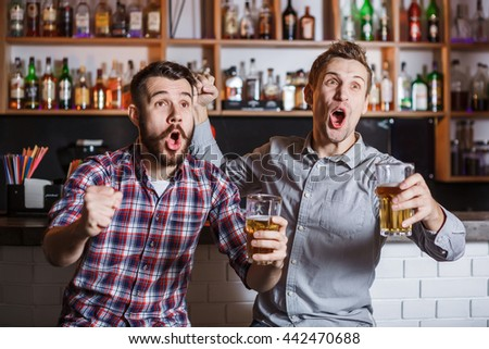 Young people with beer watching football in a bar - stock photo