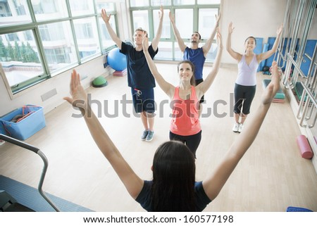 Young people with hands in air in yoga class - stock photo