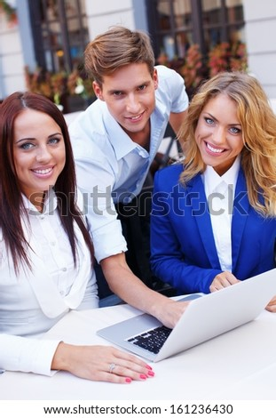 Young people with laptop discussing something in summer cafe - stock photo