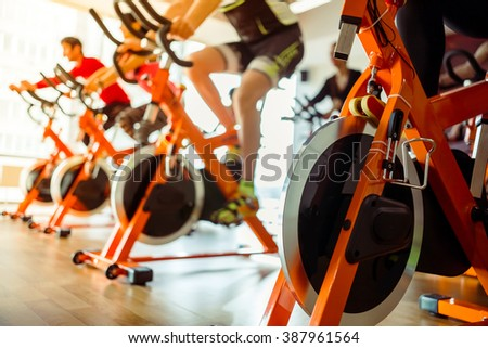 Young people working out on an exercise bike in gym, close-up - stock photo