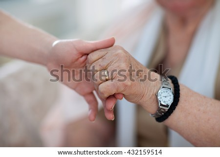 Young person is holding a hand of an old person - stock photo