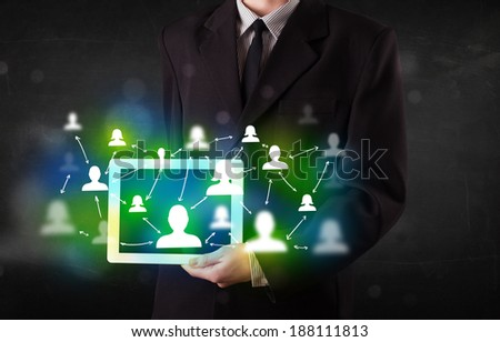 Young person presenting tablet with green social media icons and symbols