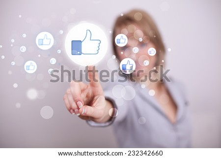 Young person pressing thumbs up button on modern social network system - stock photo