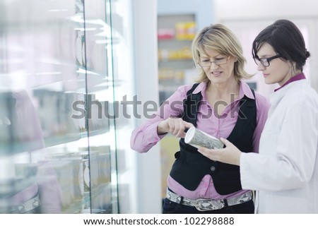 young pharmacist suggesting medical drug to buyer in pharmacy drugstore - stock photo