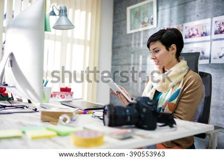 Young photographer and graphic designer at work in office