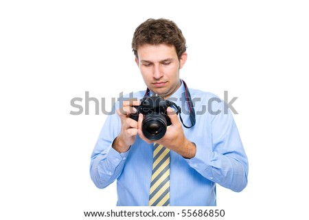 young photographer checks photos on back screen of his dslr camera, studio shoot isolated on white background - stock photo