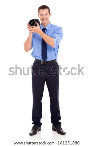young photographer holding a camera in studio - stock photo