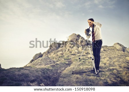 young photographer in the mountains - stock photo