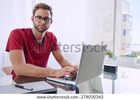 young photographer looking at the camera with a blank expression, while he works on his laptop computer with his red shirt and trimmed beard - stock photo