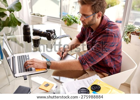 Young photographer retouching on his new laptop with his stylus and tablet on his glass desk, in his home studio - stock photo