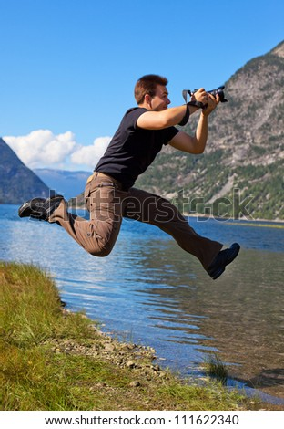 Young photographer shooting nature in the jump. - stock photo