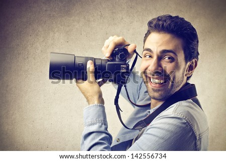 young photographer smiling with professional camera - stock photo