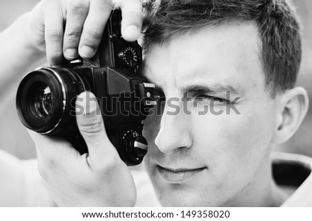 young photographer takes pictures with the old retro camera - stock photo