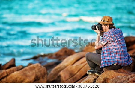 Young photographer taking photos at the beach of the beautiful seascape in sunet light - stock photo