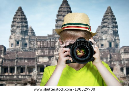 Young photographer with a camera pointing the lens directly at the viewer - stock photo