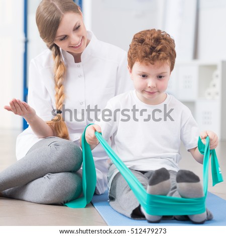 Young physiotherapist and child participating in rehabilitation