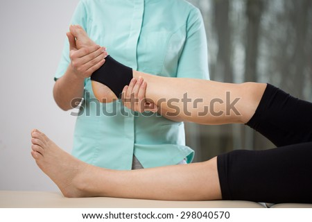 Young physiotherapist doing ankle manipulation to elderly woman - stock photo