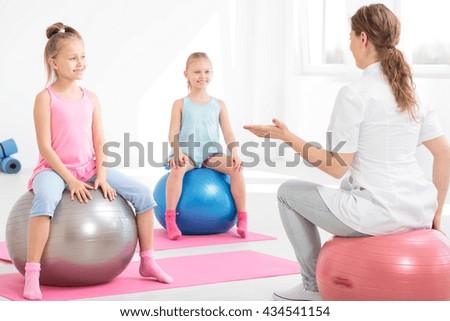 Young physiotherapist explaining exercises to smiling school girls sitting on exercise balls - stock photo