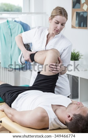 Young physiotherapist is training knee after injury - stock photo