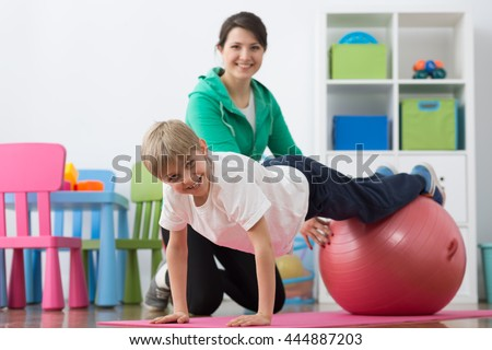 Young physiotherapist kneeling close to the boy based on hands on the foam mattress with legs on exercise ball