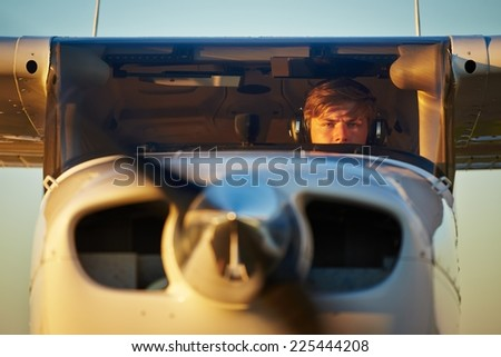 Young pilot is preparing for take off with private plane. - stock photo