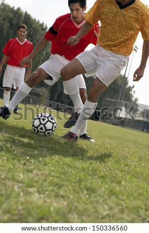 Young player playing soccer on field - stock photo