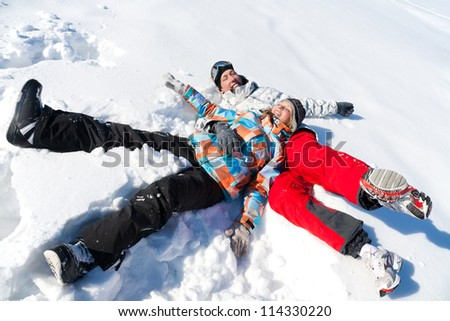 Young playful couple having fun in the snow - stock photo