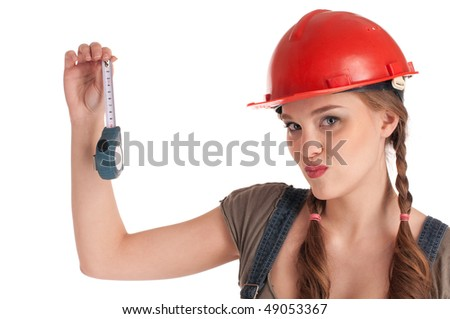 Young playful woman in jeans coverall and orange helmet holding tape measure