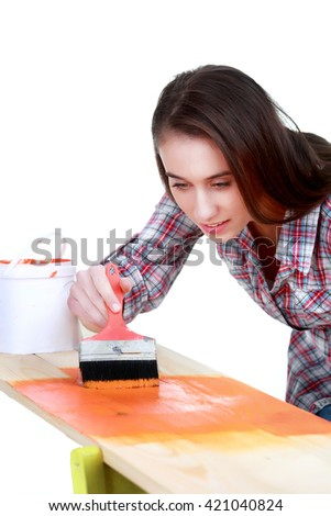 Young playful woman in shirt and jeans  painting