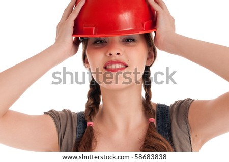 Young playful worker woman in jeans coverall and orange helmet
