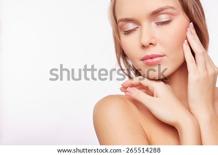 Young pleased woman with natural makeup touching her face - stock photo
