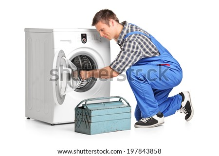 Young plumber fixing a washing machine isolated on white background