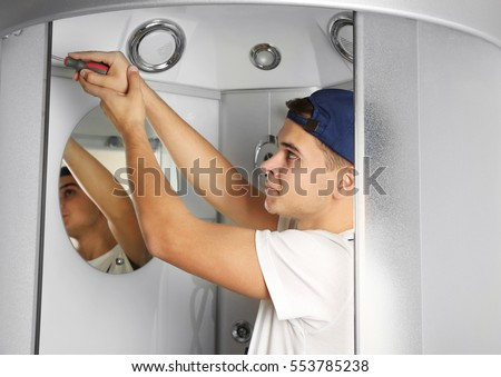Young plumber fixing shower cabin