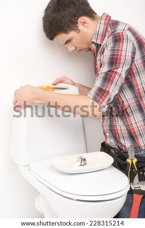 young plumber repairing flush toilet. handsome worker fixing toilet seat and looking - stock photo