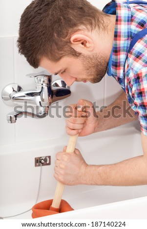 Young plumber unclogging a bathtube drain with plunger - stock photo
