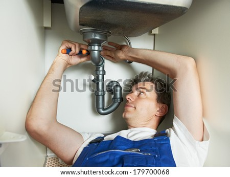 Young plumber worker working with spanner at kitchen sink repair or installation - stock photo