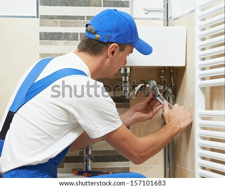 Young plumber worker working with spanner at sanitary washbasin installation system