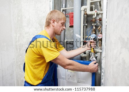 Young plumber worker working with spanner at toilet installation system - stock photo