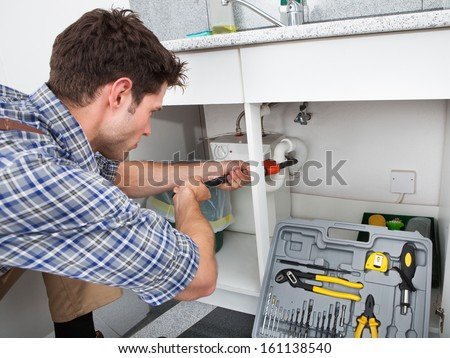 Young Plumber Working With Pipe Wrench In Kitchen - stock photo