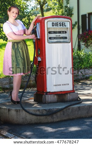 Young Plus Size Woman in dirndl at an old gas station with tap in hand