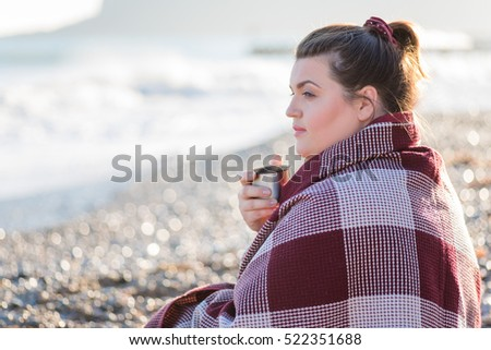 Young plus size woman resting and drinking tea on the beach. Sport concept. Healthy lifestyle. Soft focus