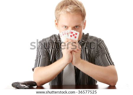 Young poker player with gun isolated on white - stock photo
