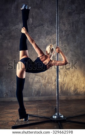 Young pole dance woman in black clothing standing backside and stretching legs - stock photo