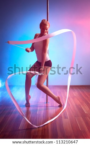 Young pole dance woman with ribbon.