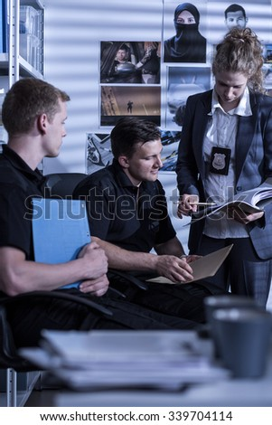 Young police officers are conducting an investigation - stock photo