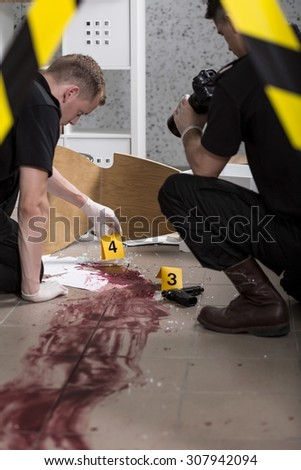 Young police officers during crime scene investigation - stock photo