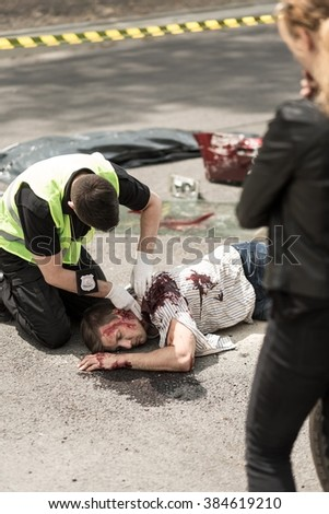 Young policeman is helping victim of car accident - stock photo