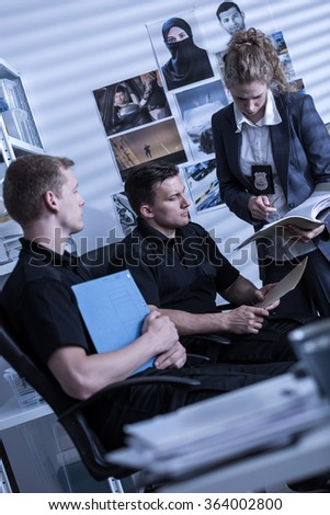 Young policewoman and policemen during criminal investigation - stock photo